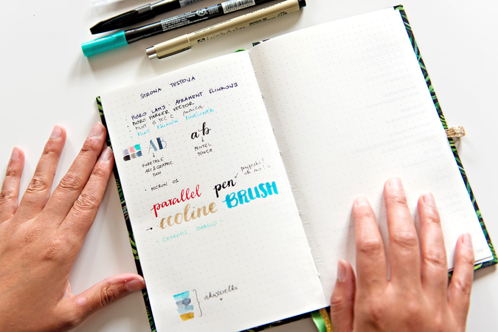 Dłonie i notatnik w kropki.