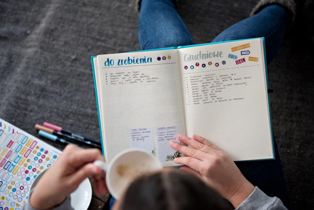 Kobieta pijąca kawę i przeglądająca planer z listą spraw do zrobienia.