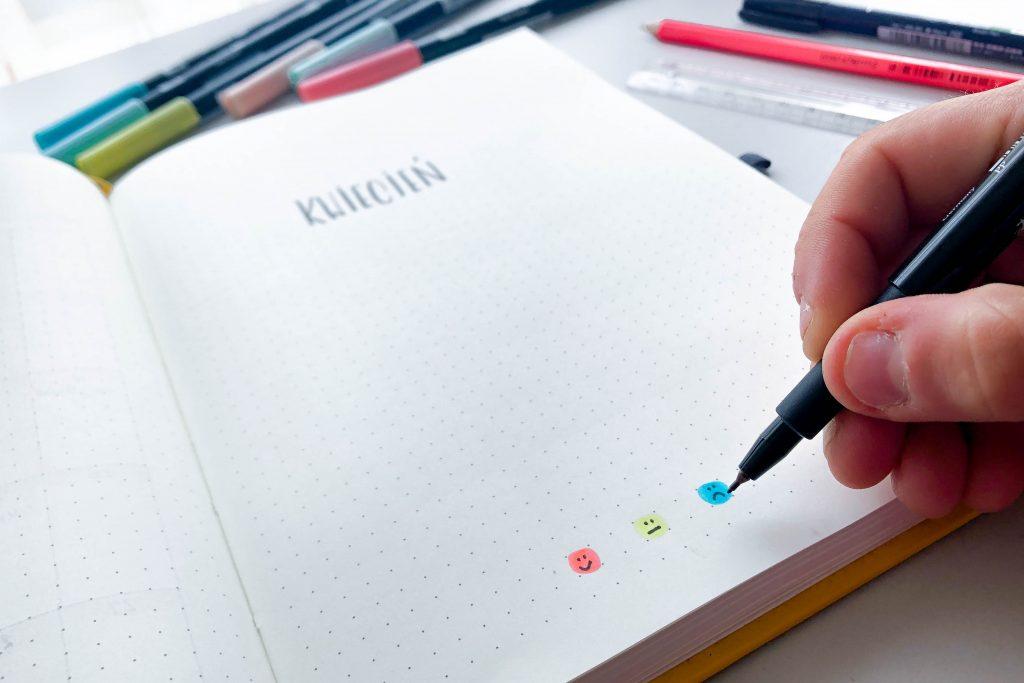 Dłoń pisząca w notesie w kropki.