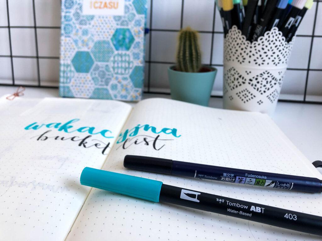 Strona tytułowa w notesie w kropki i brush peny.