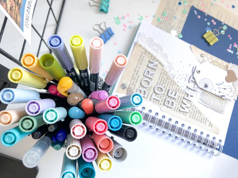 Kolorowe brush peny w kubku i notes na spirali.