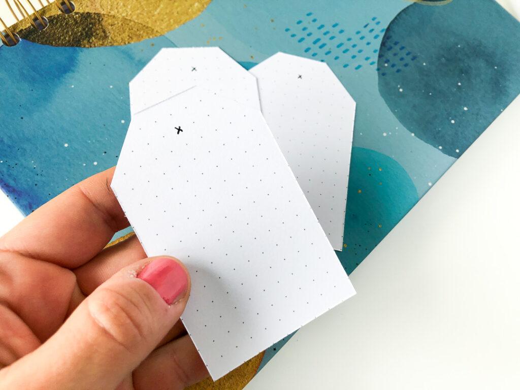Notes w kropki kreatywny chill. Tagi do prezentów trzymane w dłoni.