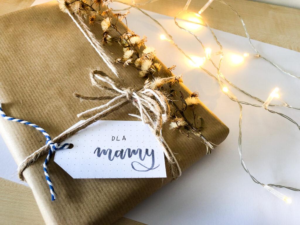 Prezent świąteczny zapakowany w szary papier. W tle światełka.