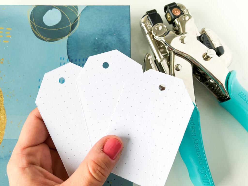 Notes w kropki. Damska dłoń trzyma tagi do prezentów. W tle dziurkacz cropadile.