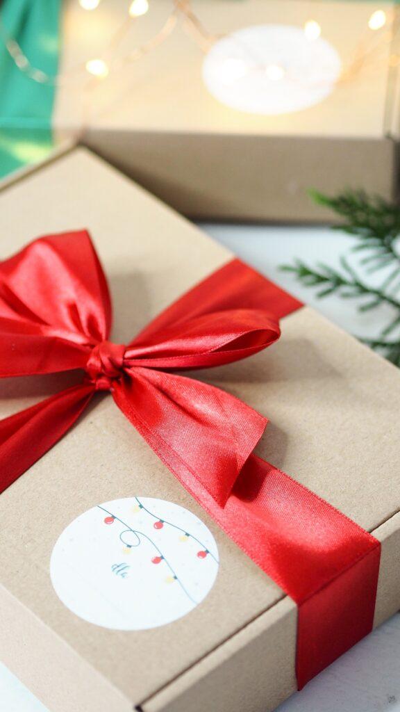 Świąteczny prezentownik. Pomysły na prezenty. Prezent świąteczny, pudełko z czerwoną kokardą.
