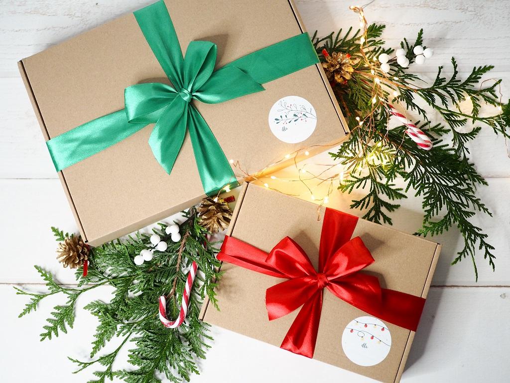 Świąteczny prezentownik. Pomysły na prezenty powyżej 100 zł.Zdjęcie dwóch prezentów świątecznych z kokardami. W tle gałązki choinkowe.