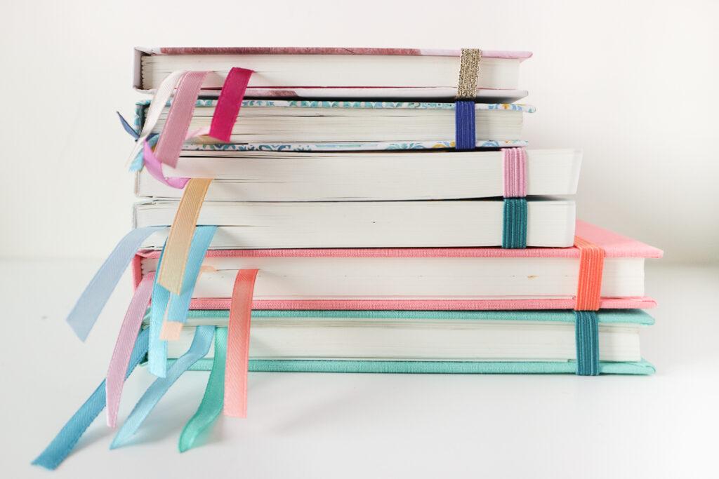 Stos planerów i notesów z kolorowymi tasiemkami.