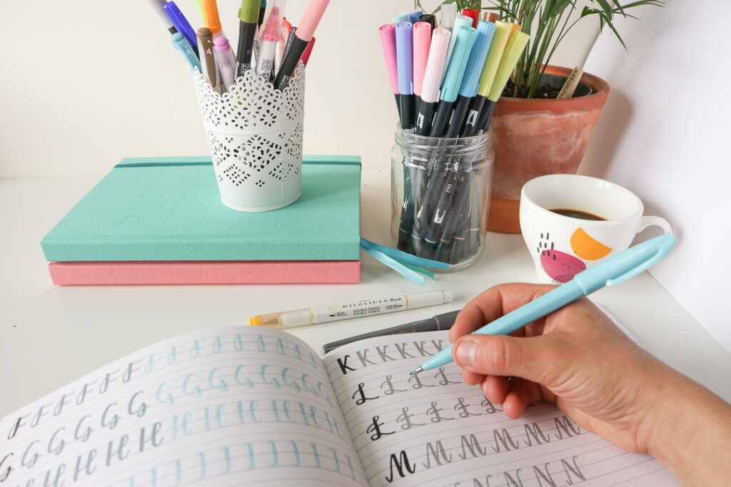 Osoba pisząca w planerze. Brush lettering