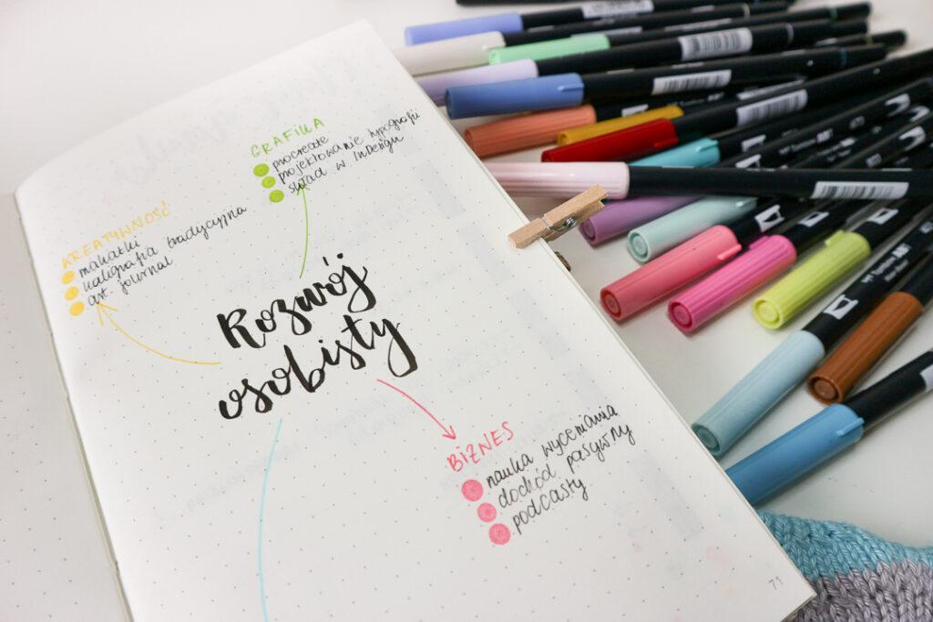 Plan rozwoju osobistego w notesie w kropki i kolorowe brush peny.
