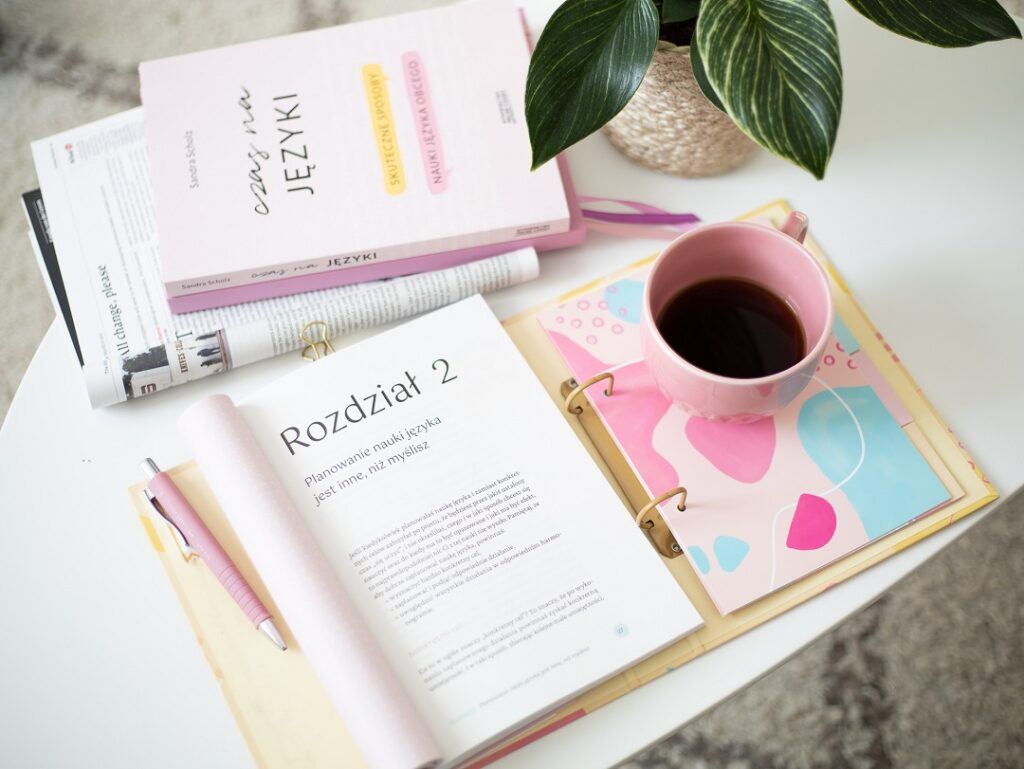 Książka, segregator, gazeta, kawa i kwiatek.