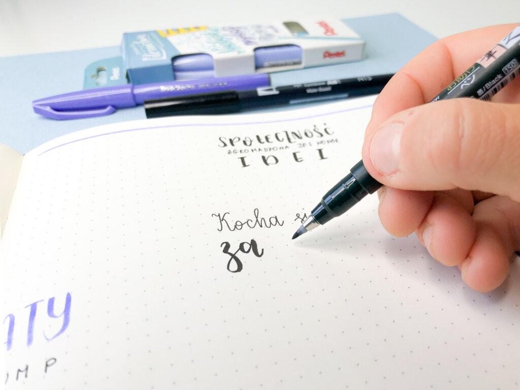 Dłoń pisząca w notesie w kropki. W tle brush peny.