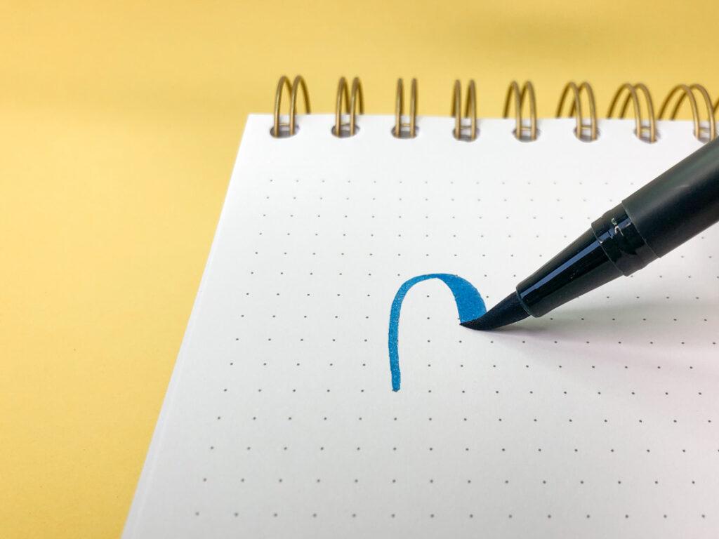 Niebieski brush pen piszący po kartce.