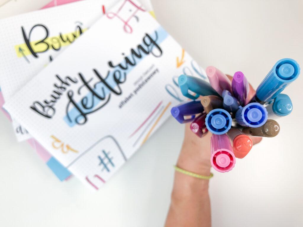 Dłoń trzymająca brush peny i zeszyty do brush letteringu.