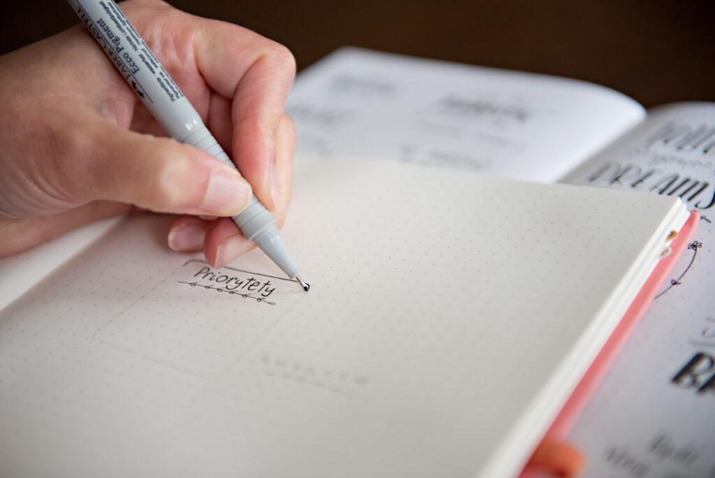 Ręka pisząca w planerze pełnym czasu.