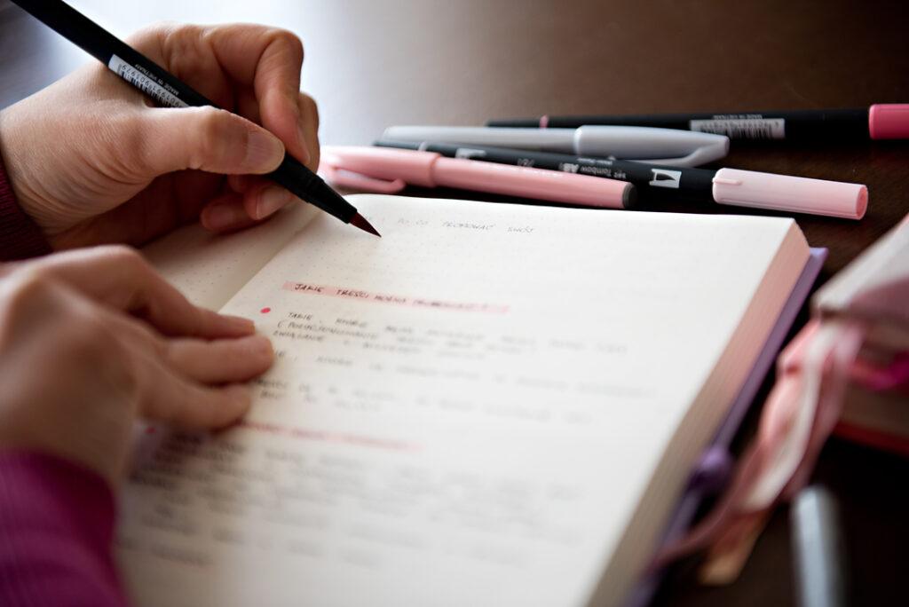 Ręka pisząca w lawendowym planerze.