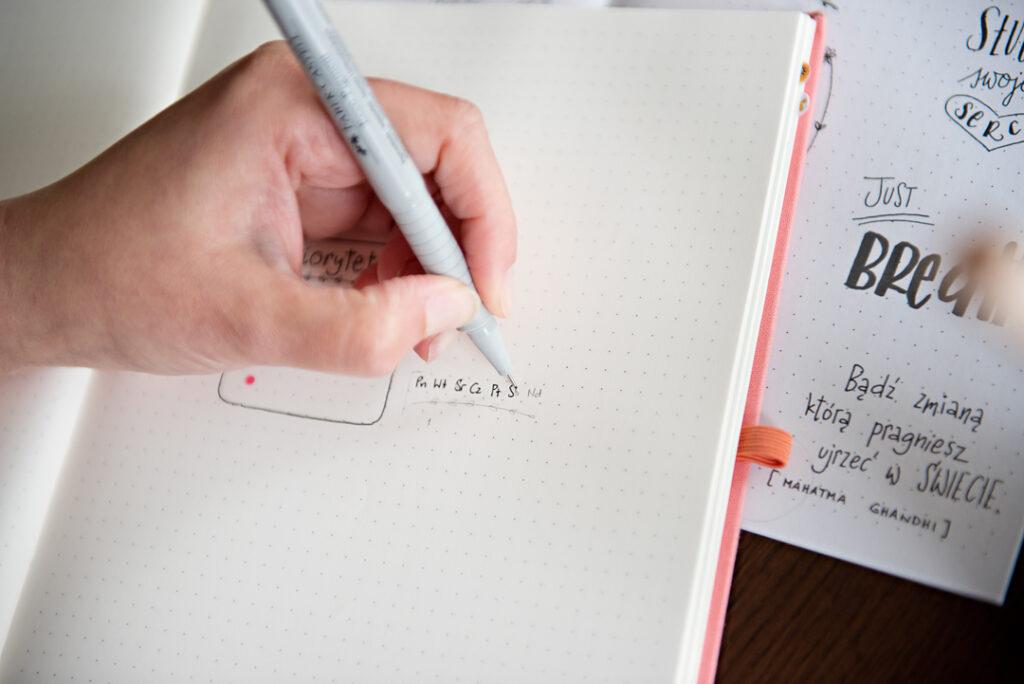 Dłoń trzymająca cienkopis i pisząca w planerze.