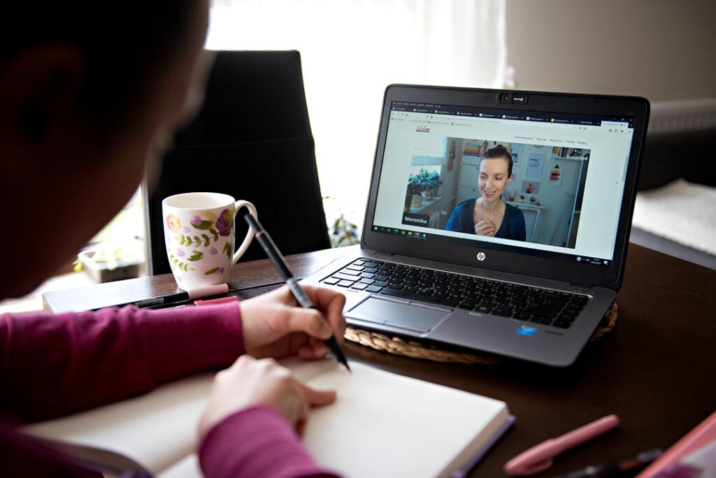 Kobieta robiąca notatki i oglądająca webinar.