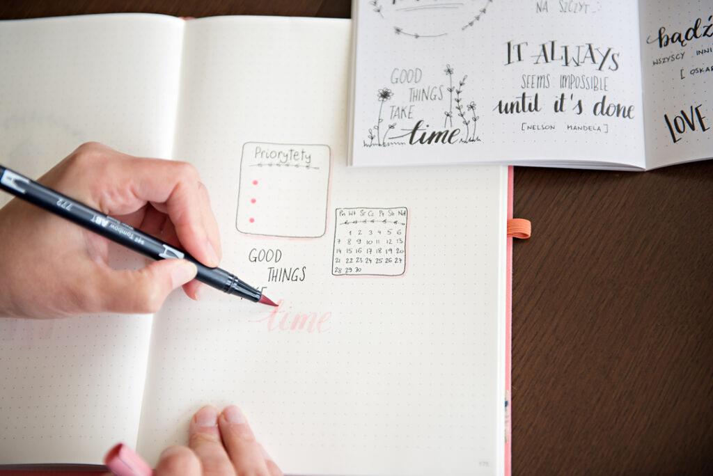 Ręka pisząca w bullet journalu.