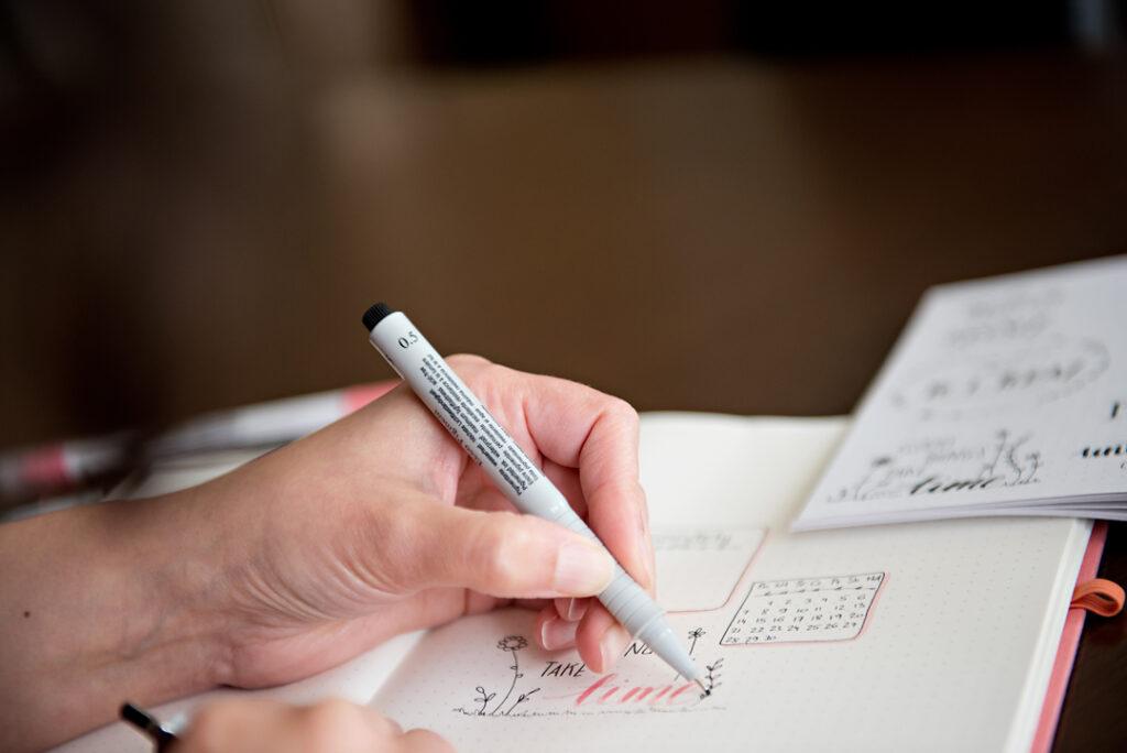 Dłoń pisząca w planerze w kropki.