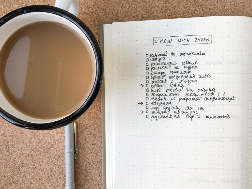 Lipcowa lista zadań w notesie i kubek z kawą.