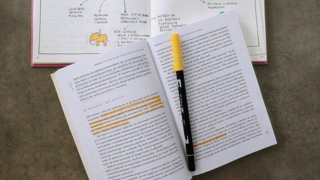 Książka z zakreślaczem i notes z notatkami.