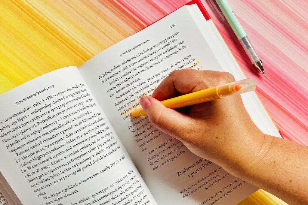 Ręka zakreślająca fragment w książce.