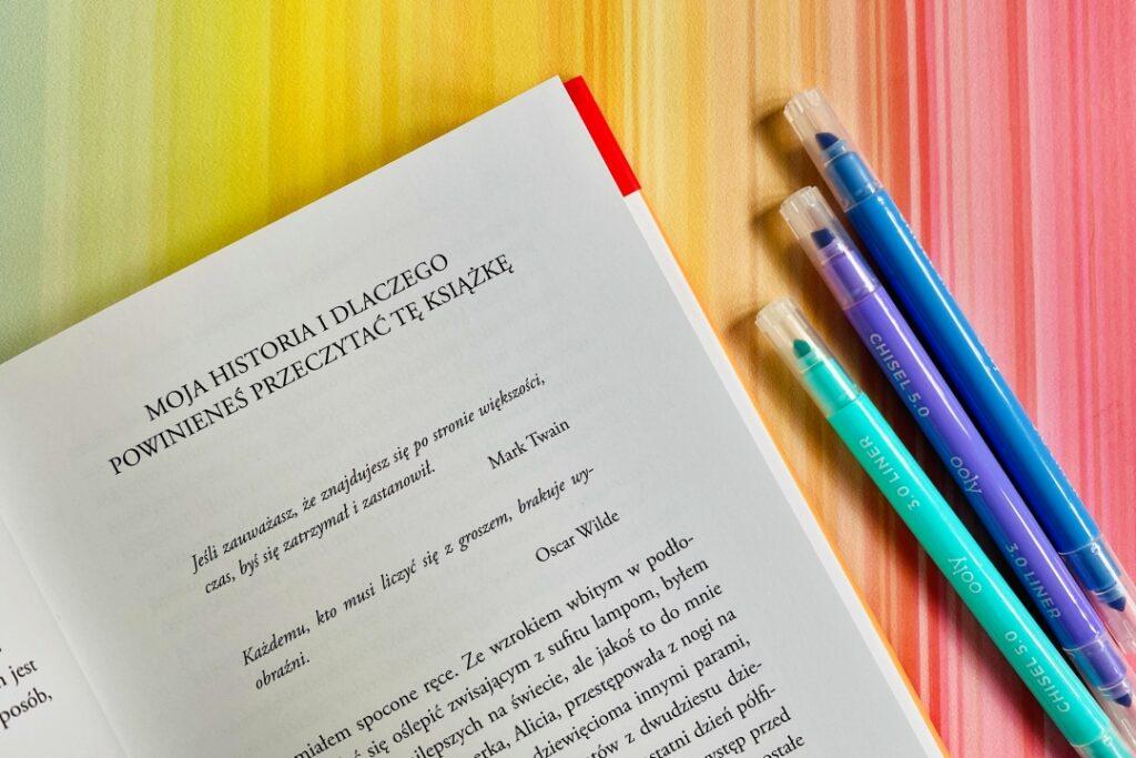 Książka i kolorowe zakreślacze.